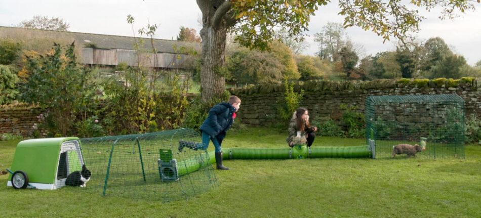 Deux enfants qui jouent dehors avec deux lapins dans un tunnel Zippi relié au clapier d'extérieur Eglu Go