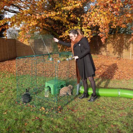 Une femme dehors en automne avec deux lapins dans leur enclos
